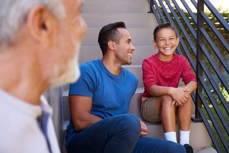 Smiling Multi-Generation Male Hispanic Family Sitting On Steps In Garden And Talking Together Standard-Bild