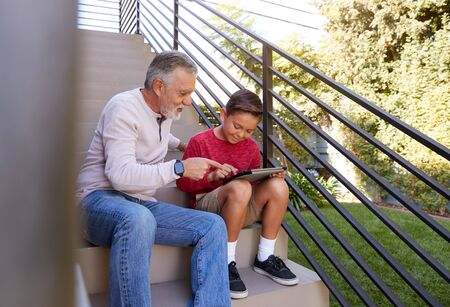 Grandfather Sitting On Steps Outdoors At Home With Grandson Using Digital Tablet