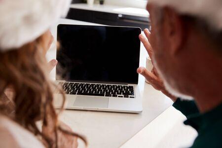 Senior Hispanic Couple Wearing Santa Hats With Laptop Having Video Chat With Family At Christmas 免版税图像