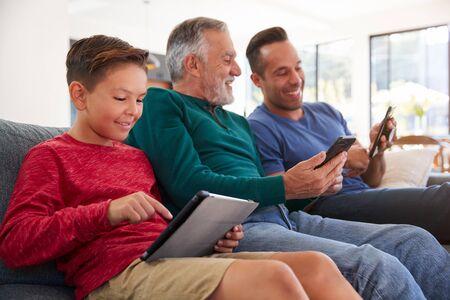 Multi-Generation Male Hispanic Family Sitting On Sofa At Home Using Mobile Phones And Digital Tablet Standard-Bild