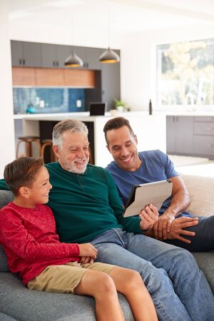 Multi-Generation Male Hispanic Family Sitting On Sofa At Home Watching Movie On Digital Tablet
