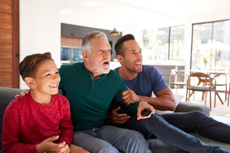Excited Multi-Generation Male Hispanic Family Sitting On Sofa At Home Watching Sports On TV