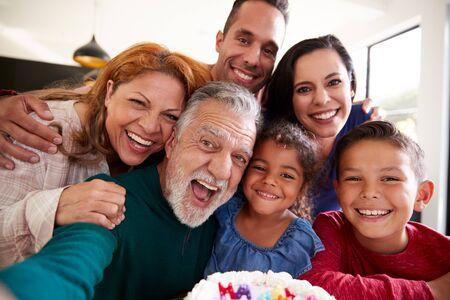 Une famille hispanique multigénérationnelle prend un selfie pour célébrer l'anniversaire de sa petite-fille à la maison