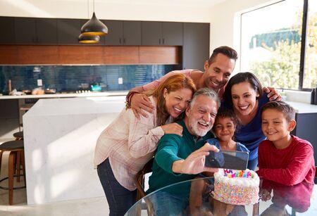 Hispanische Familie mit mehreren Generationen macht Selfie, um den Geburtstag der Enkelinnen zu Hause zu feiern Standard-Bild