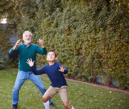 Grandfather And Grandson Waiting To Catch Ball In Back Yard