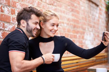 Young Couple On Date Taking Selfie On Mobile Phone Sitting At Outdoor Coffee Shop Table Together