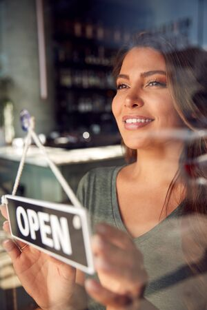 Female Owner Of Start Up Coffee Shop Or Restaurant Turning Round Open Sign On Door Stok Fotoğraf