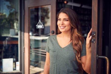 Female Owner Of Start Up Coffee Shop Or Restaurant Standing In Doorway