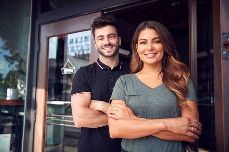Portrait Of Couple Starting New Coffee Shop Or Restaurant Business Standing In Doorway Stok Fotoğraf