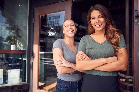 Portrait Of Two Women Starting New Coffee Shop Or Restaurant Business Standing In Doorway