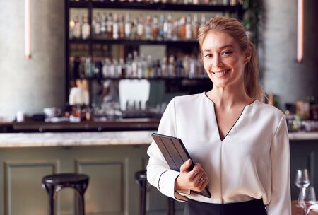 Portrait Of Confident Female Owner Of Restaurant Bar Standing By Counter Holding Digital Tablet