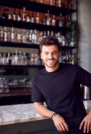 Portrait Of Confident Male Owner Of Restaurant Bar Leaning Against Counter