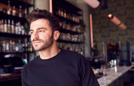 Portrait Of Confident Male Owner Of Restaurant Bar Standing By Counter
