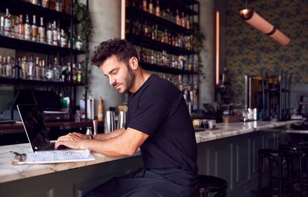 Male Owner Of Restaurant Bar Sitting At Counter Working On Laptop Stok Fotoğraf