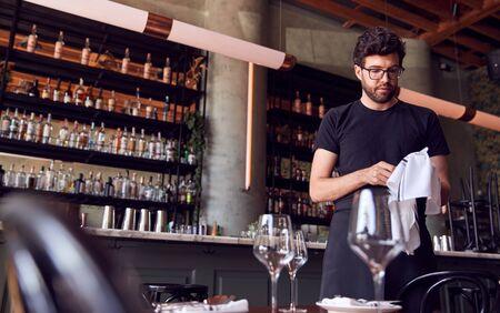 Male Waiter Polishing Glasses Before Service In Bar Restaurant