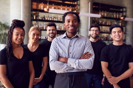 Portrait Of Male Owner Of Restaurant Bar With Team Of Waiting Staff Standing By Counter Stok Fotoğraf