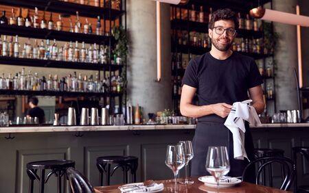 Portrait Of Male Waiter Polishing Glasses Before Service In Bar Restaurant