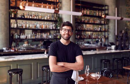Portrait Of Male Waiter Standing In Bar Restaurant Before Service Stok Fotoğraf