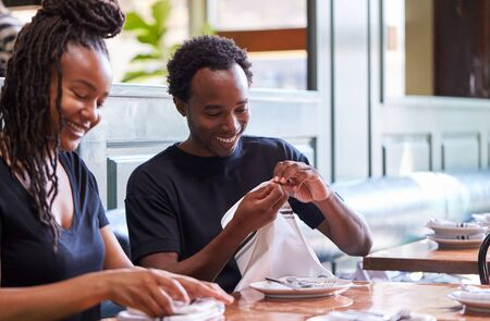 Male And Female Waiters Folding Napkins In Restaurant Before Service Archivio Fotografico