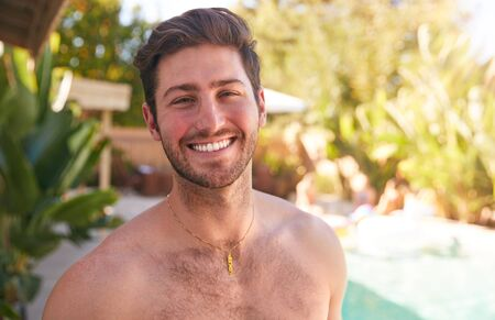 Portrait Of Smiling Bare Chested Man Outdoors With Friends At Summer Pool Party