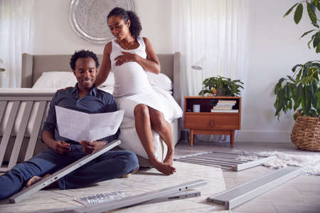 Couple With Pregnant Woman Looking At Instructions For Self Assembly Baby Cot