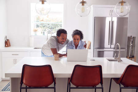 Couple Wearing Pyjamas Standing In Kitchen Working From Home On Laptop