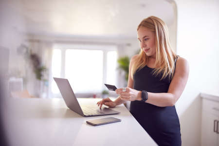 Pregnant Woman In Kitchen Making Online Credit Card Purchase On Laptop Archivio Fotografico
