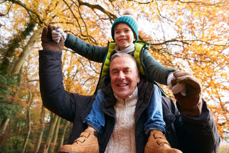 Portrait Of Grandfather Giving Grandson Ride On Shoulders As They Walk Along Autumn Woodland Path