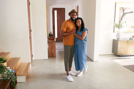 Portrait Of Loving African American Couple Hugging In Hall At Home Foto de archivo