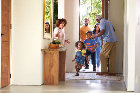 Grandparents At Home Opening Door To Visiting Family With Children Running Ahead