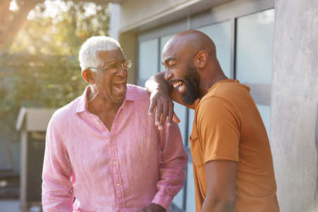 Senior Father Talking And Laughing With Adult Son In Garden At Home Stock Photo