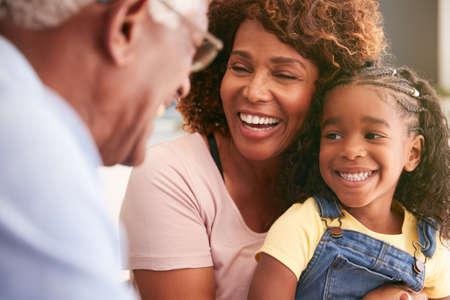 Close up Of Loving Grandparents Cuddling Granddaughter At Home