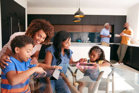 Grandmother With Mother Helping Grandchildren To Use Digital Tablets On Table At Home