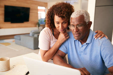 Senior African American Couple Using Laptop To Check Finances At Home