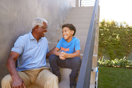 Grandfather With Grandson Sitting On Steps And Talking Outdoors At Home Reklamní fotografie