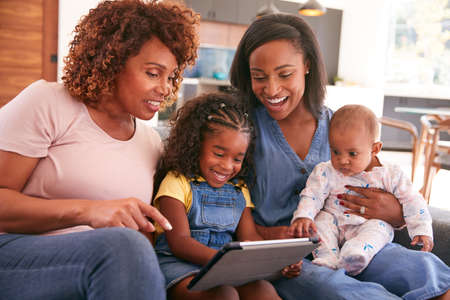 Multi-Generation Female African American Family Sitting On Sofa At Home Using Digital Tablet