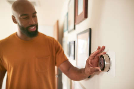 Man Adjusting Digital Central Heating Thermostat At Home Foto de archivo