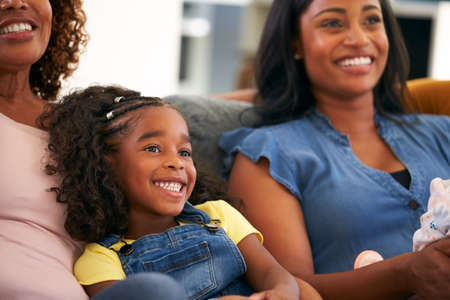 Granddaughter With Grandmother And Mother Relaxing At Home Sitting On Sofa Watching TV Together