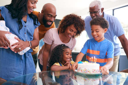 Multi-Generation African American Family Celebrating Daughters Birthday At Home Together