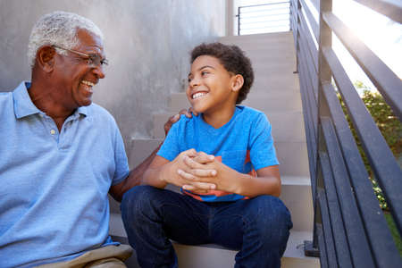 Grandfather With Grandson Sitting On Steps And Talking Outdoors At Home