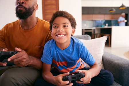 African American Father And Son Sitting On Sofa At Home Playing Video Game Together