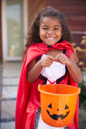 Portrait Of Girl Wearing Fancy Dress Outside House Collecting Candy For Trick Or Treat