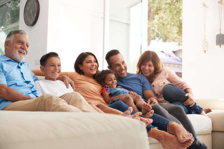 Multi-Generation Hispanic Family Relaxing At Home Sitting On Sofa Watching TV Together Stockfoto