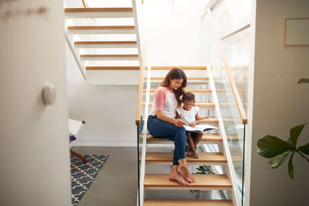 Hispanic Mother And Daughter Sitting On Staircase In Modern Home Reading Book Together
