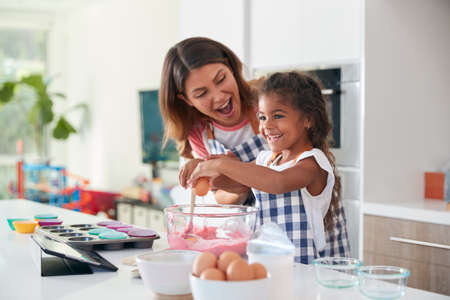 Hispanic Mother And Daughter Having Fun In Kitchen At Making Cake Together
