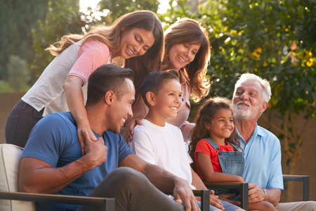 Multi-Generation Hispanic Family Relaxing In Garden At Home Together Stockfoto