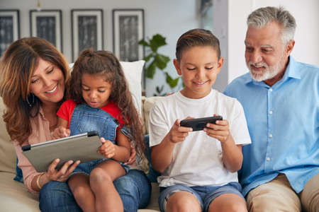 Grandchildren And Grandparents Using Digital Tablet And Mobile Phone At Home