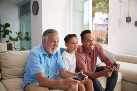 Multi-Generation Male Hispanic Family Playing Video Game At Home Sitting On Sofa Together