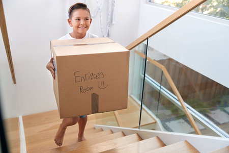 Hispanic Boy Carrying Box Into New Home On Moving Day