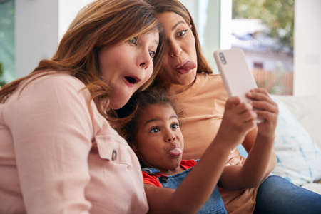 Multi-Generation Female Hispanic Family At Home Pulling Funny Faces For Selfie On Mobile Phone